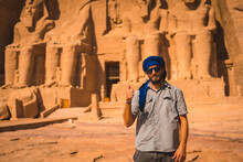 A Young Tourist With A Blue Turban Visiting The Abu Simbel Temple In Southern Egypt In Nubia Next To Lake Nasser. Temple Of Pharaoh Ramses II, Travel Lifestyle