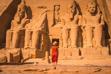 A Young Tourist In A Red Dress Entering The Abu Simbel Temple In Southern Egypt In Nubia Next To Lake Nasser. Temple Of Pharaoh Ramses II
