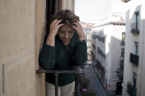 dramatic lifestyle portrait of mature woman on her 70s crying depressed and sad at home balcony feeling desperate suffering anxiety problem in senior female depression