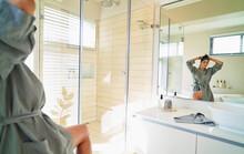 Woman In Bathrobe Fixing Hair ...