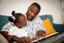 Affectionate Father And Daughter Playing Keyboard Piano On Sofa