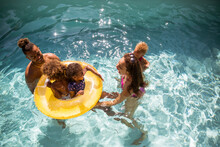 Happy Family Playing In Inflatable Ring In Sunny Summer Swimming Pool