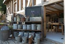 Vintage Watering Cans On Display Below Plant Nursery Exit Sign