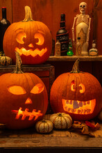 Silly And Scary Carved Lit Pumpkins  With Bottles Of Potions For Halloween