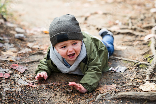 Boy hurt after falling in the forest sad and unhappy child crying Canvas