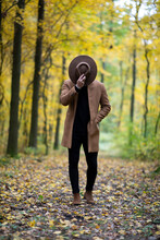 Man With Cowboy Hat Covering His Face In The Forest