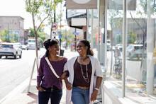 Happy Women Friends Walking Arm In Arm On Sunny City Sidewalk