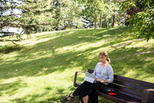 Woman Using Digital Tablet On Park Bench