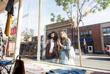 Women Friends Window Shopping At Sunny Storefront