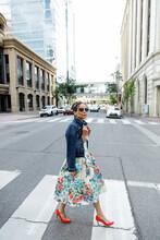 Portrait Stylish Woman In Floral Dress Crossing City Street