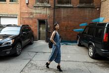 Stylish Teenage Girl Walking In Urban Alley