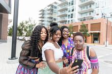 Stylish Young Women Friends Taking Selfie On City Street Corner
