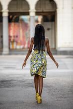 Stylish Woman In Skirt Walking In Urban Alley