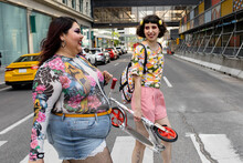 Happy Stylish Young Women Friends Crossing City Street At Crosswalk