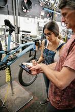 Bike Shop Mechanics With Smart Phone Fixing Bike In Workshop