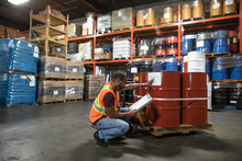Man Working On Inventory Control In Distribution Warehouse