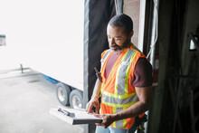 Distribution Warehouse Worker Looking At Clipboard By Dock Door