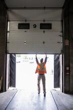 Distribution Warehouse Worker Opening Dock Door