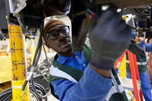 Male Transit Worker Fixing Equipment In Maintenance Facility