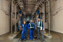 Portrait Of Men And Woman Standing On Railroad Track In Subway Train Workshop