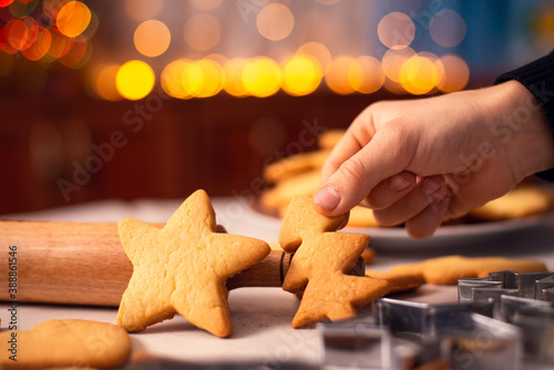 Foto Cookies in star and christmas tree shapes on the table near rolling pin and baking accessories