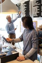 Male Worker At Cash Register In Marijuana Dispensary