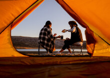 Two Young Girlfriends Traveler Took A Break, Sit In Front Of The Lake And Drink Hot Drinks Near The Tent