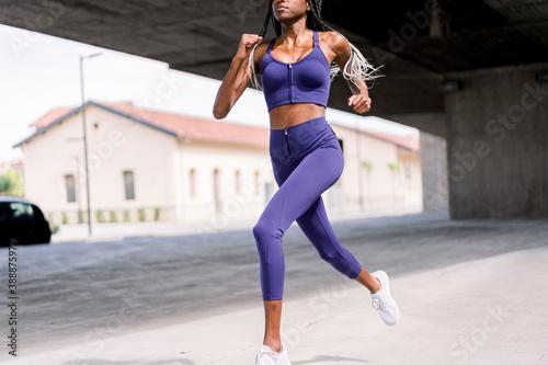 African American sportswoman running in city Fototapet