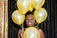 Happy Woman With Yellow Balloons Looking At Camera