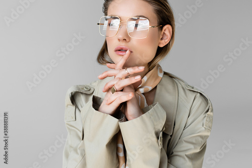 Obraz trendy woman in glasses, trench coat and scarf posing on grey - fototapety do salonu