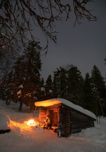 A Man Sits In The Night Winter Forest Near The Fire