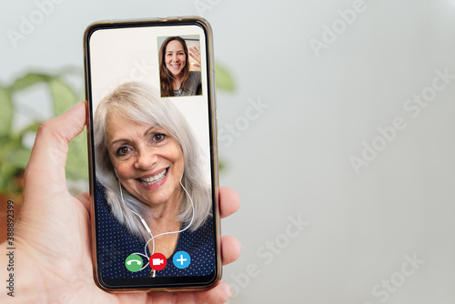 Canvas Happy senior and daughter talking on video call with mobile phone during coronav