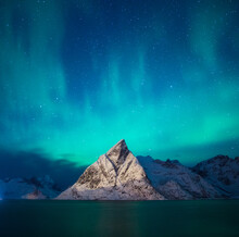 Aurora Borealis Over A Snowy Mountain