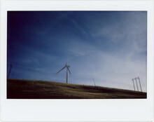 A Wind Turbine On Top Of A Hill