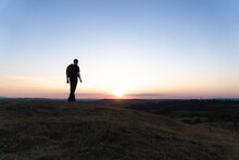 A Hiker Walking On Top Of A Hill. Silhouetted Against The Sunset.