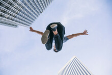 Young Man Performing Parkour Against Sky In City