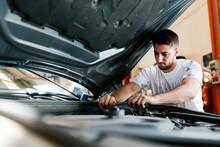 Young Man Repairing Car While ...