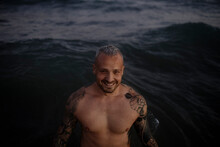 Smiling Shirtless Mid Adult Man Standing In Sea