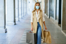 Woman With Face Mask Carrying Bag While Walking At Store Lobby In City