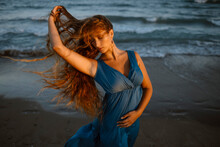 Woman With Hand Dancing At Beach During Sunset