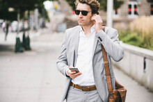 Businessman Connecting In-ear Headphones With Mobile Phone While Standing At Sidewalk In City