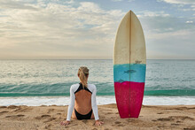 Woman Sitting By Surfboard On ...