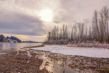 Cold Early Morning With Sun Blazing In A Cloudy Sky In Mid-winter Along The Flathead River, Northwestern Montana