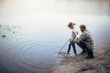 Father Holding Daughter During Fishing By Lake