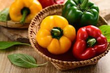 Fresh Yellow, Red And Green Bell Peppers In A Bamboo Basket On Wooden Background, Organic Vegetables