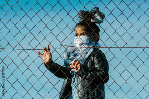 Fotografía Latin young girl wearing a mask, looking away with an serious expression, behind a fence, in a blue sky background