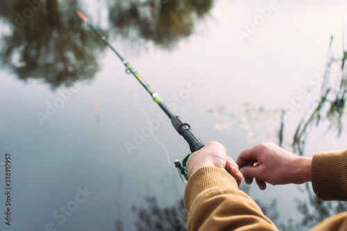 Fotografija Man fisherman catches a fish on a fishing rod with a reel on the lake against the background of the forest and sky with clouds