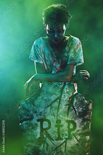 Photo zombie gloats next to headstone