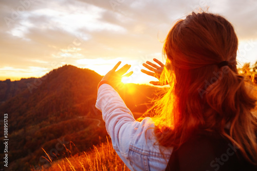 Obraz Carefree hipster girl enjoying nature on top of mountain with sunset. - fototapety do salonu