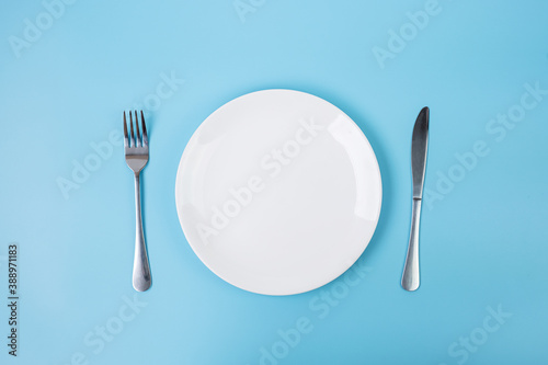 Fotografering empty white ceramics plate with knife and fork on blue background